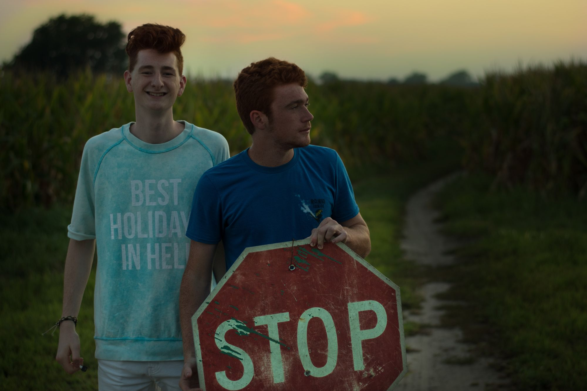 Deux garçons faisant du stop au bord de la route