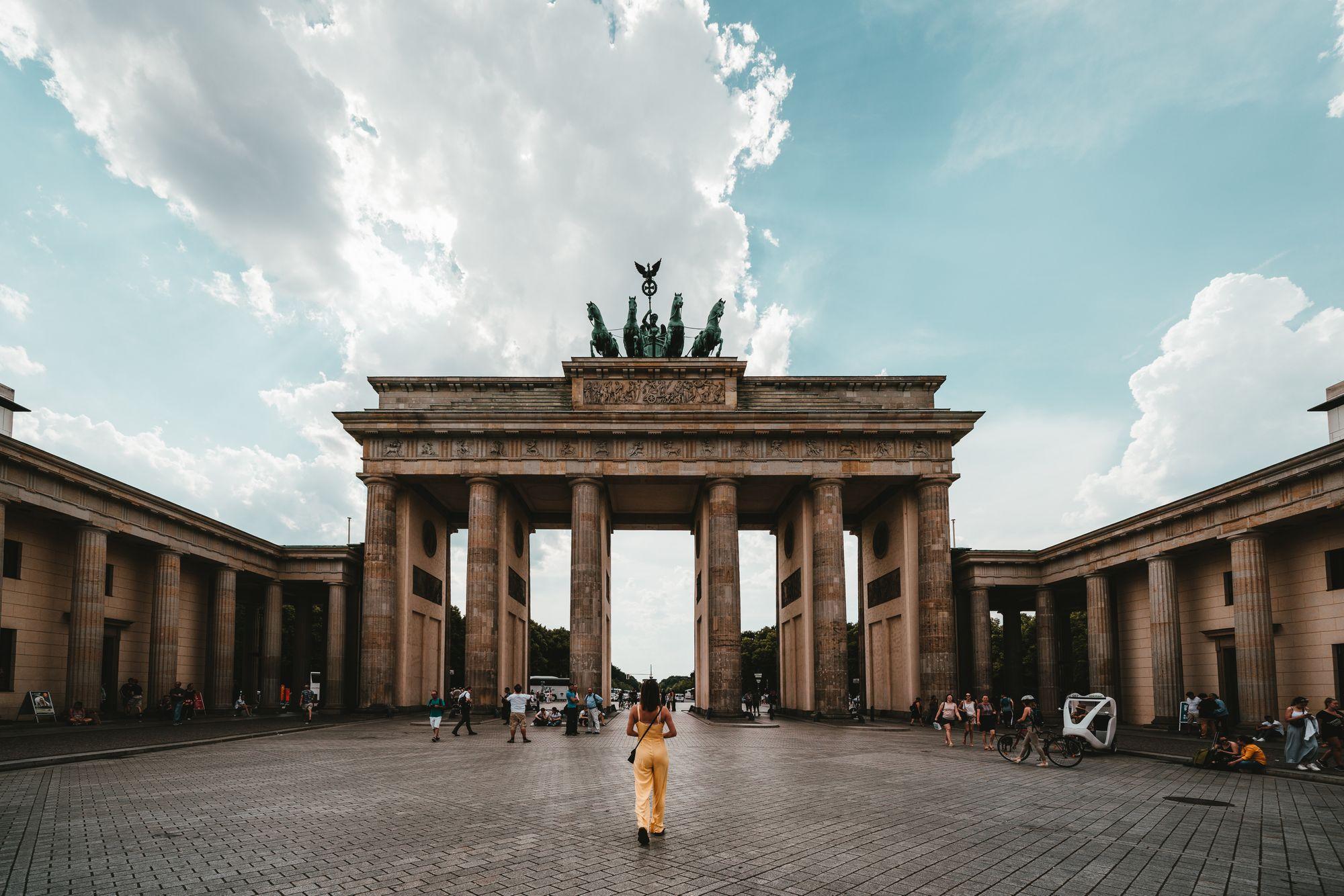 Femme devant la Porte de Brandebourg sur la place de Paris à Berlin en Allemagne