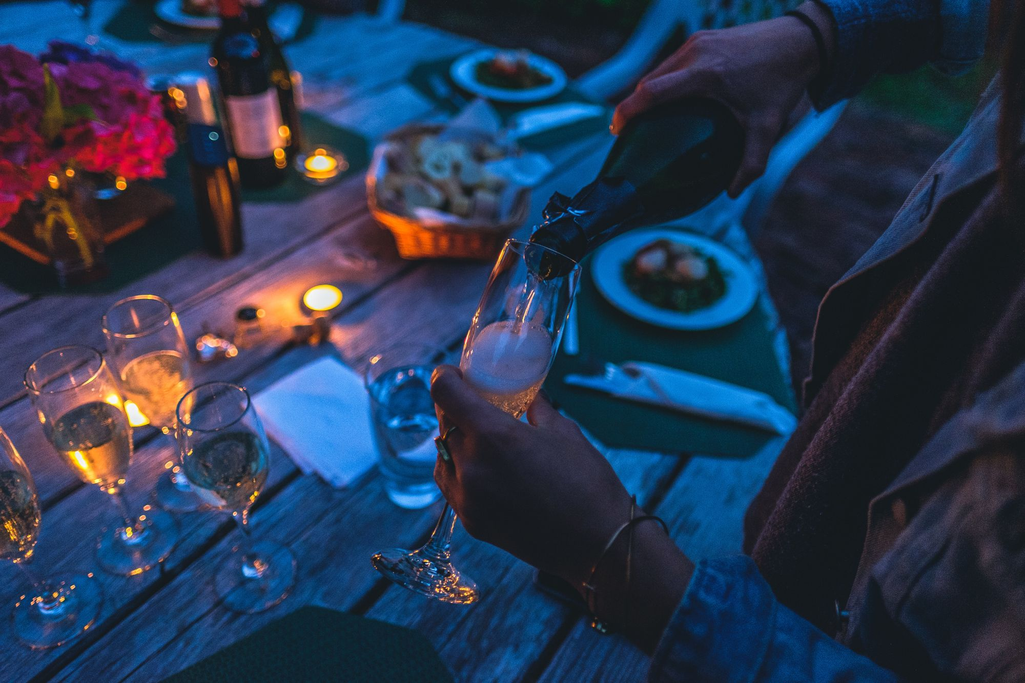 femme tenant une coupe pour servir du champagne pendant un dîner