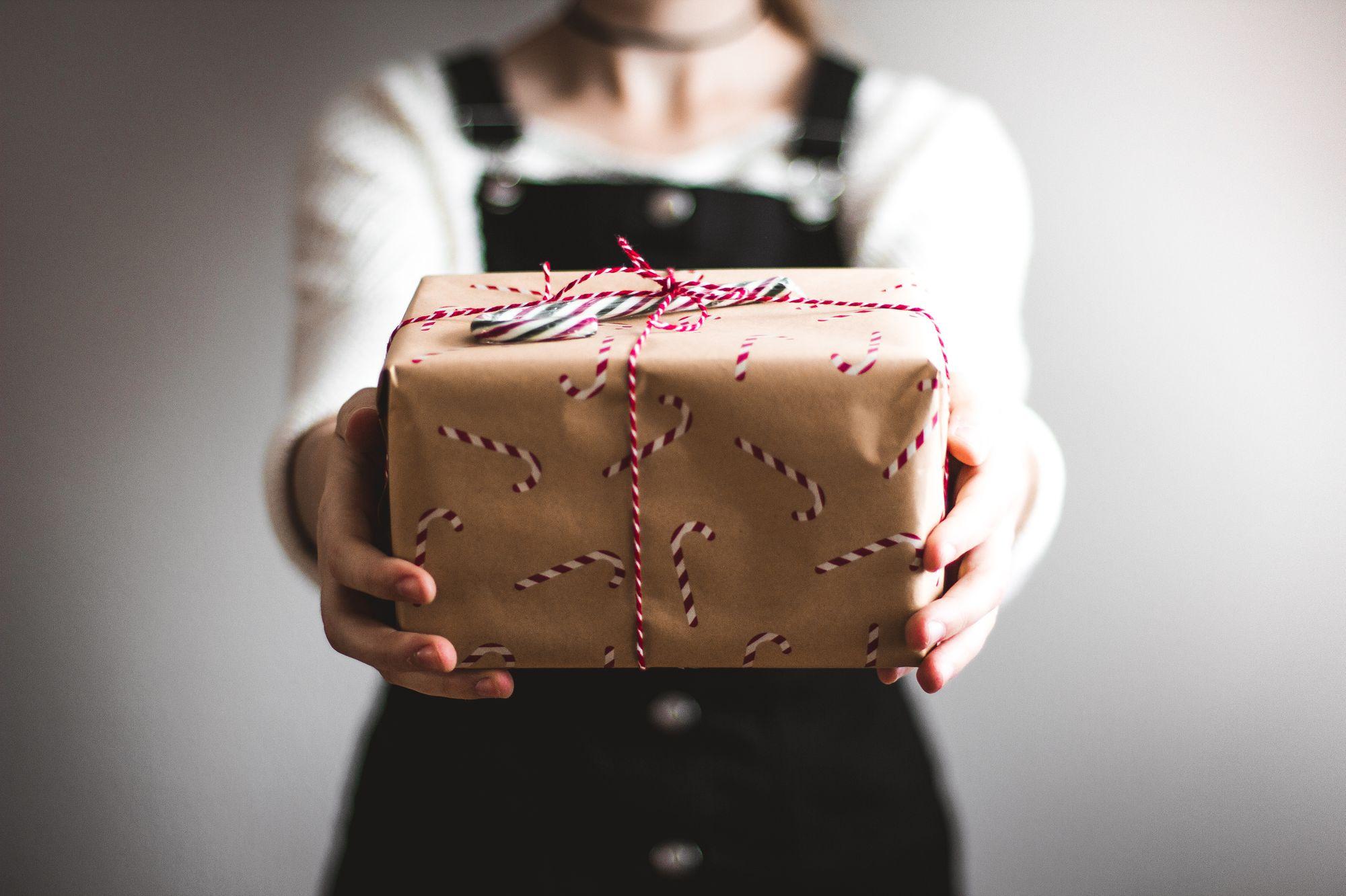 Personne portant un cadeau de Noël emballé dans du papier cadeau
