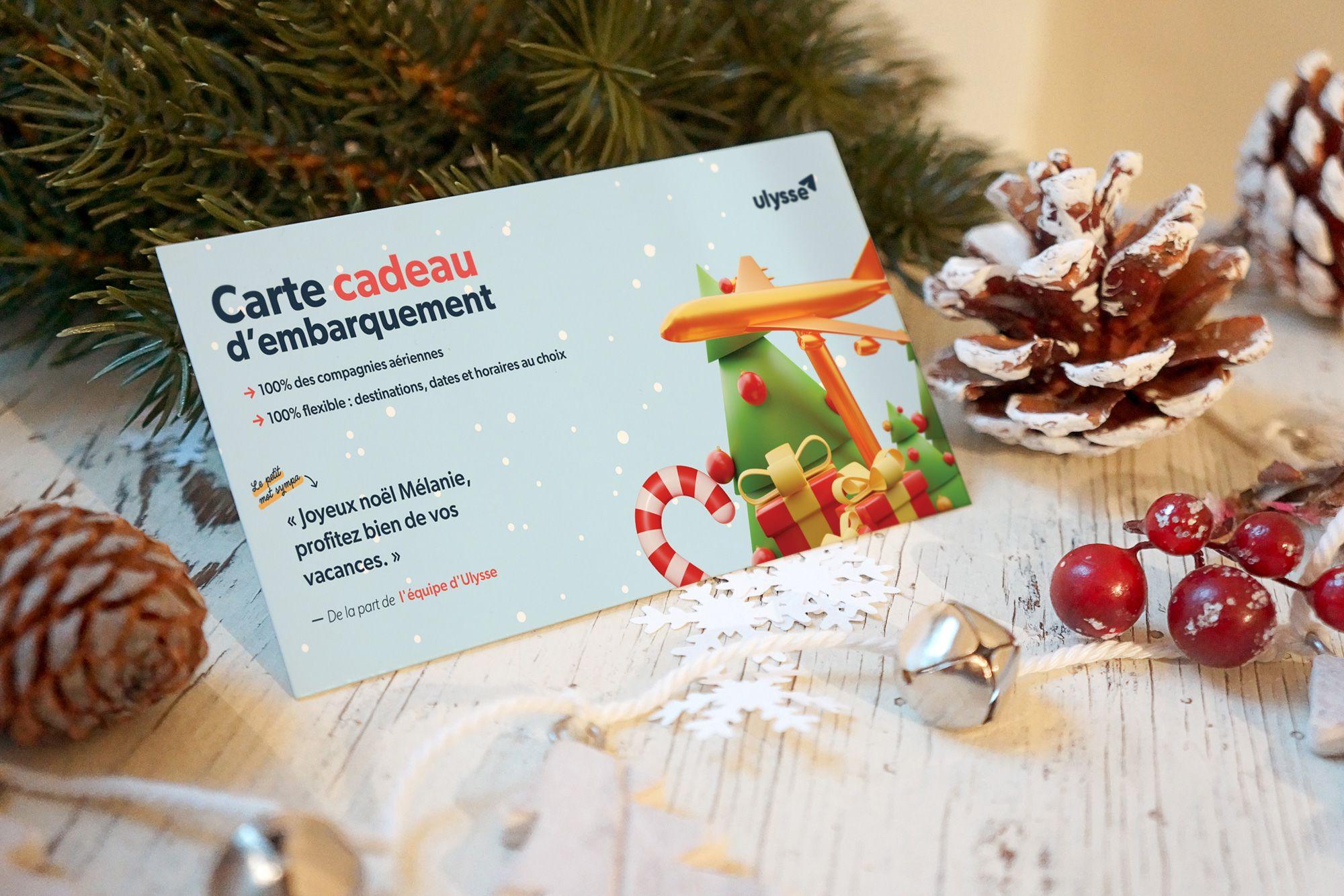 Carte cadeau de Noël Ulysse posée sur une table entourée de décorations de noël