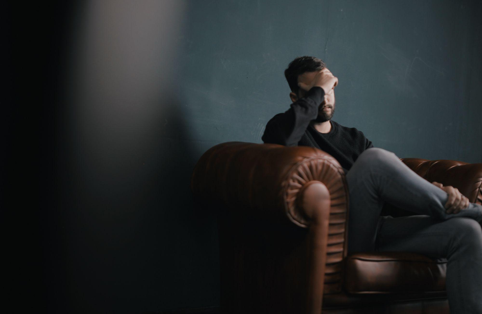 homme assis sur un fauteuil en cuir marron qui se tient la tête