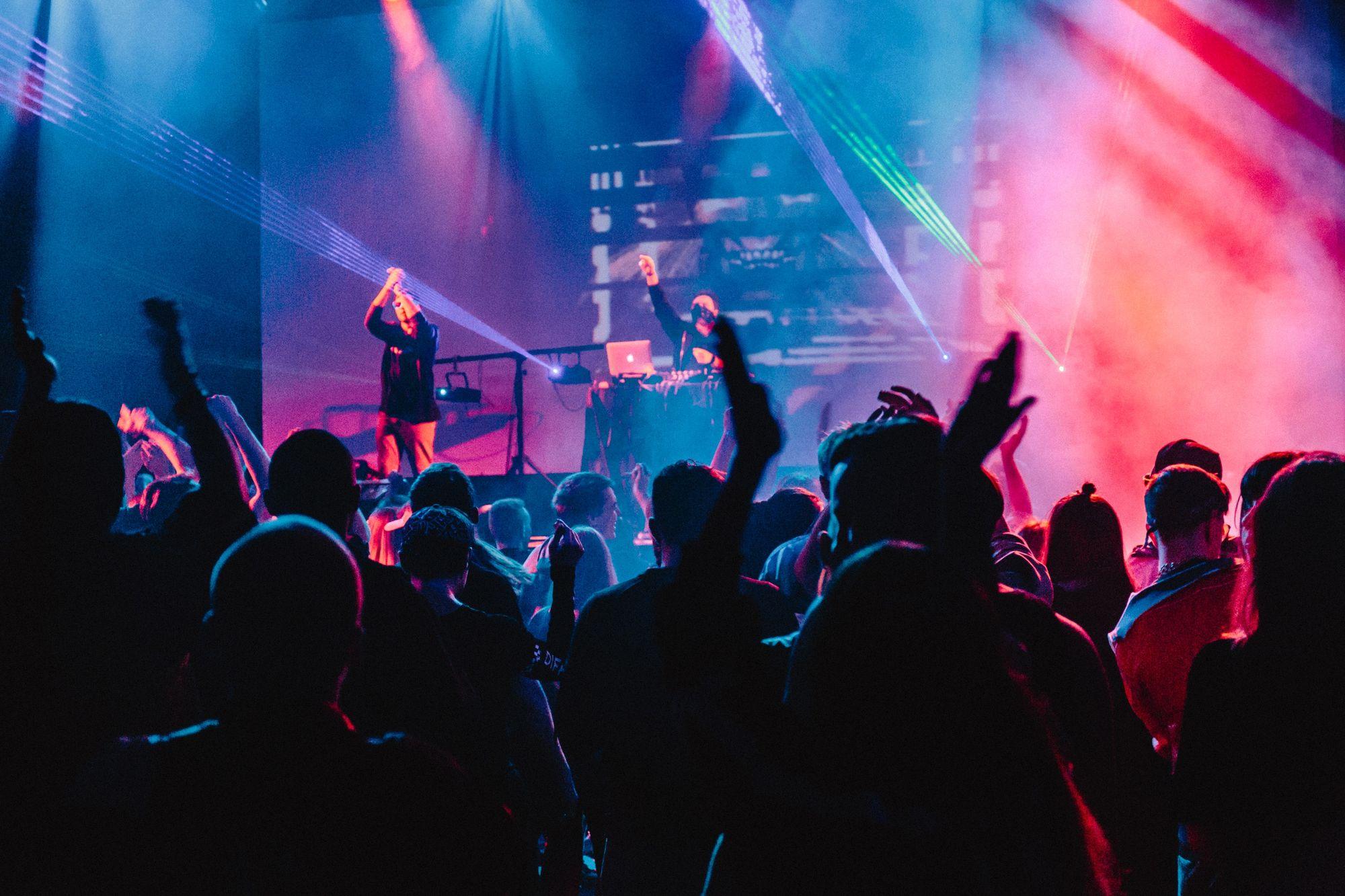 personnes dansant à un concert devant une scène