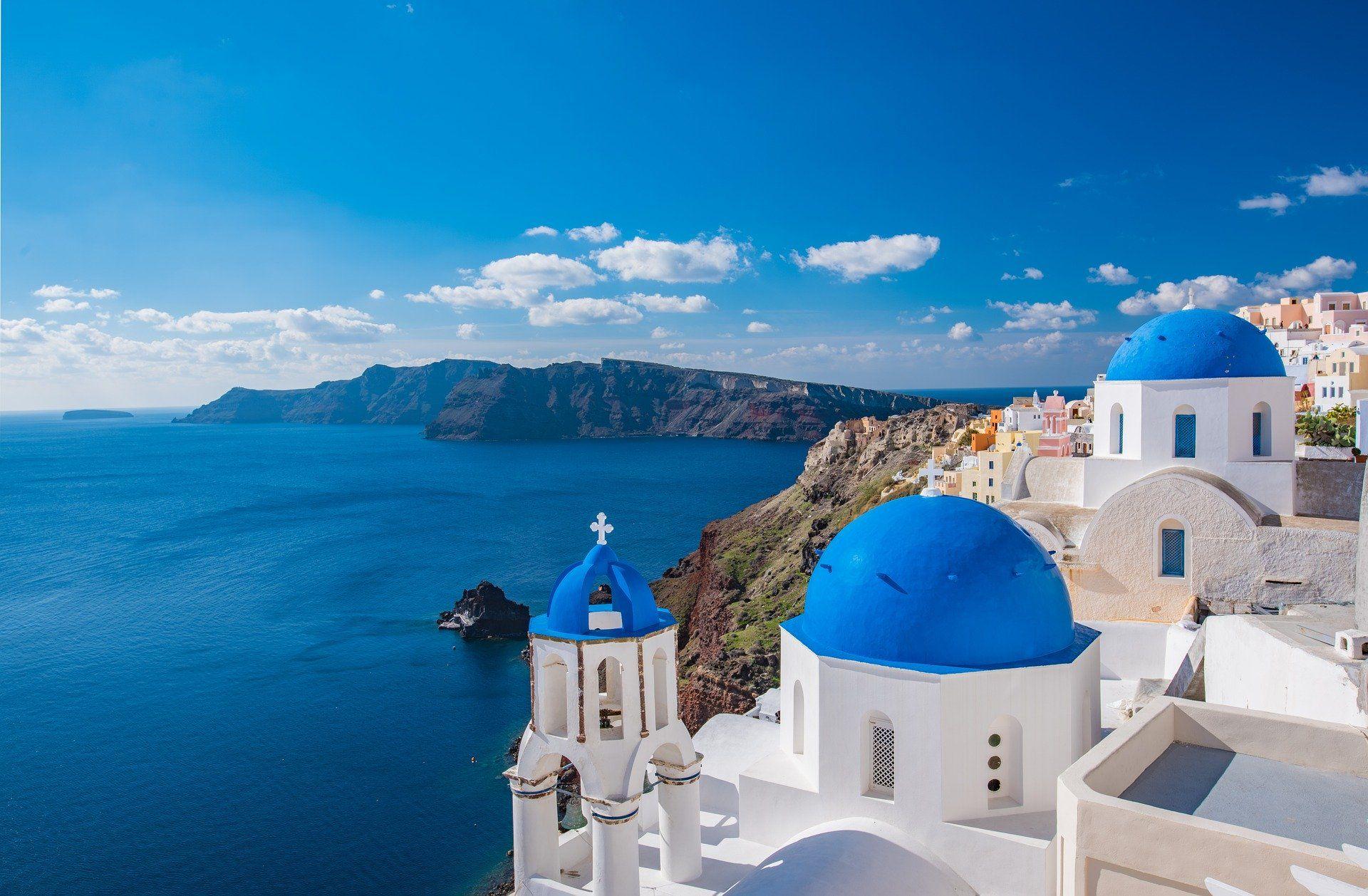 vue sur la mer Égée et les dômes bleus de la ville d'Emporio sur l'île de Santorin en Grèce