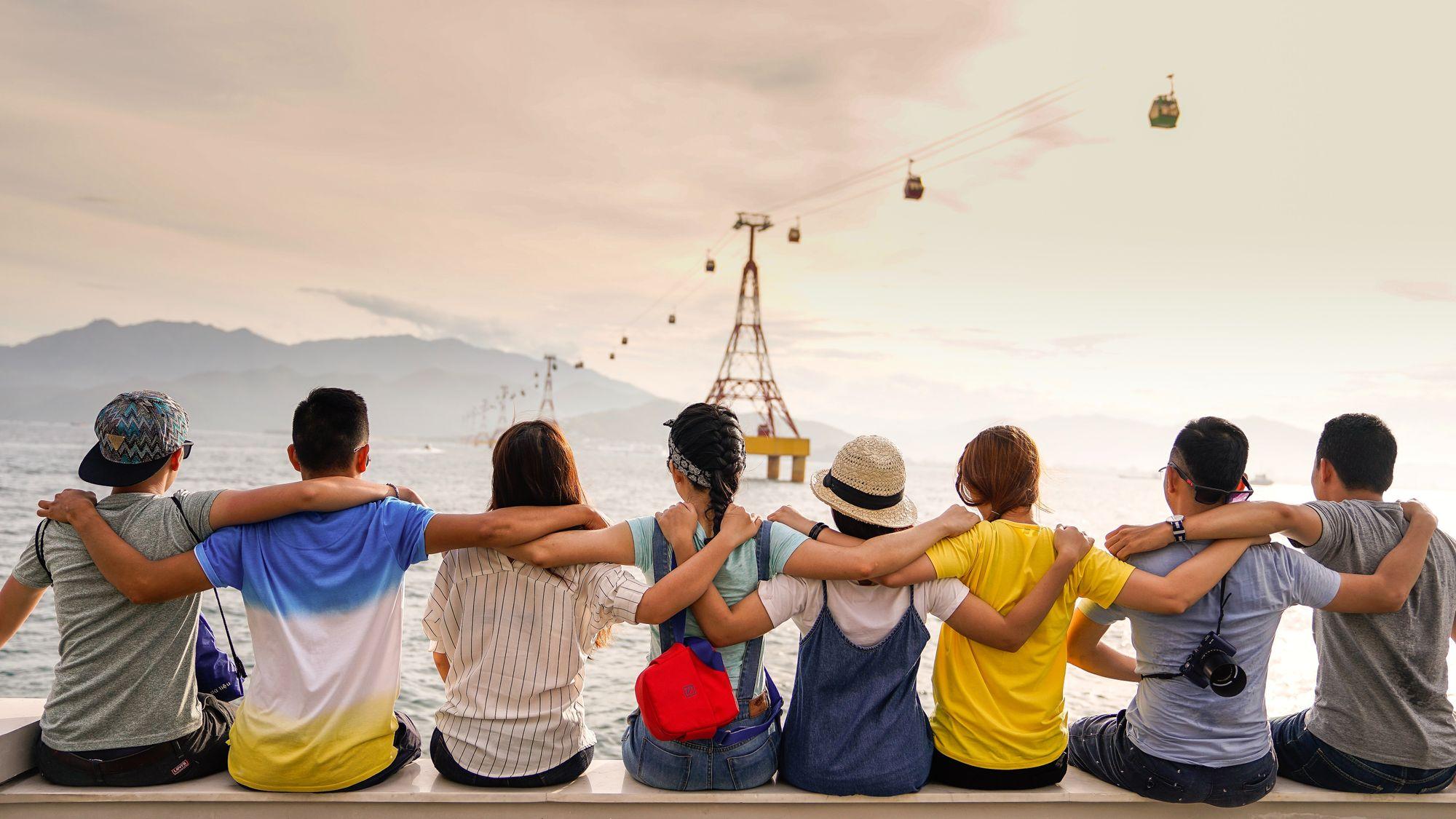 personnes se tenant par les épaules assis sur un mur