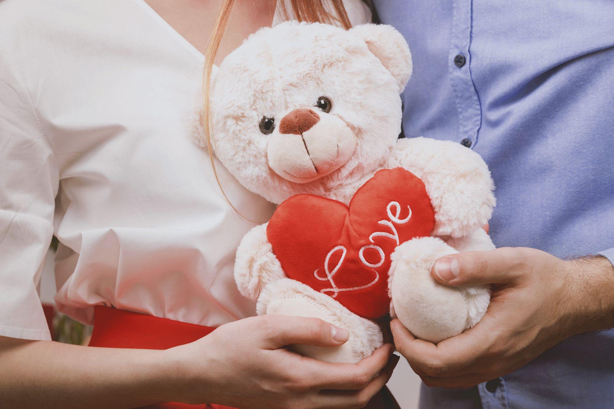 deux personnes tenant un ours en peluche dans leurs mains