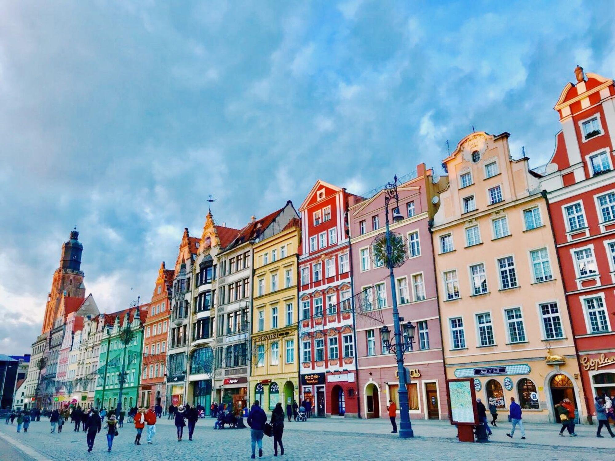gens marchant sur le trottoir devant des maisons colorées dans la ville de Wroclaw en Pologne