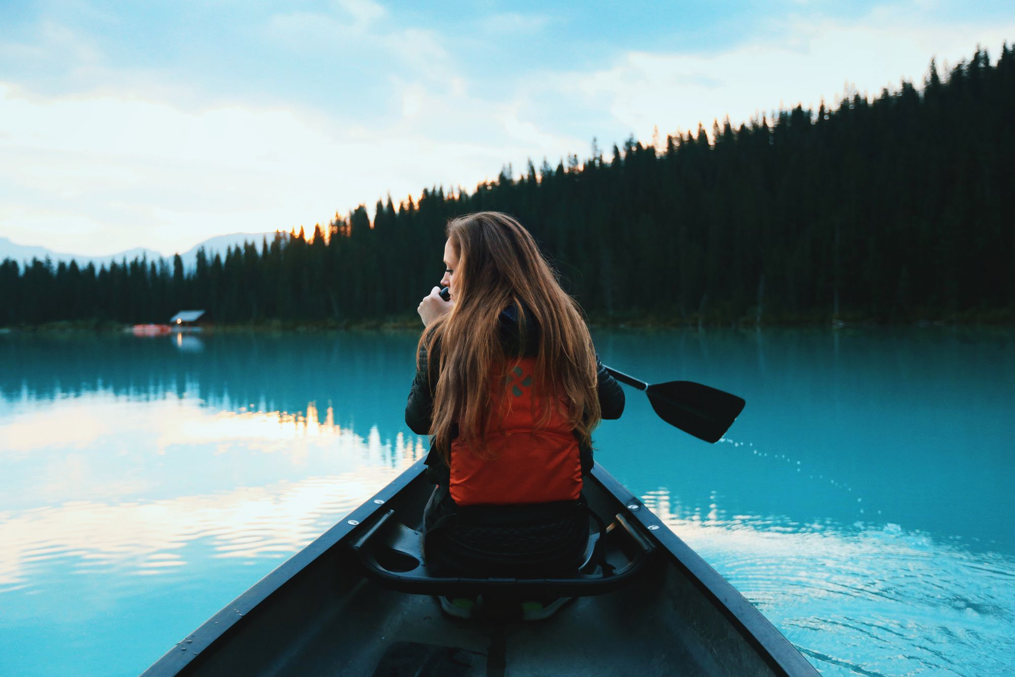 femme tenant une rame sur un bateau sur le Lac Louis du parc national de Banff au Canada