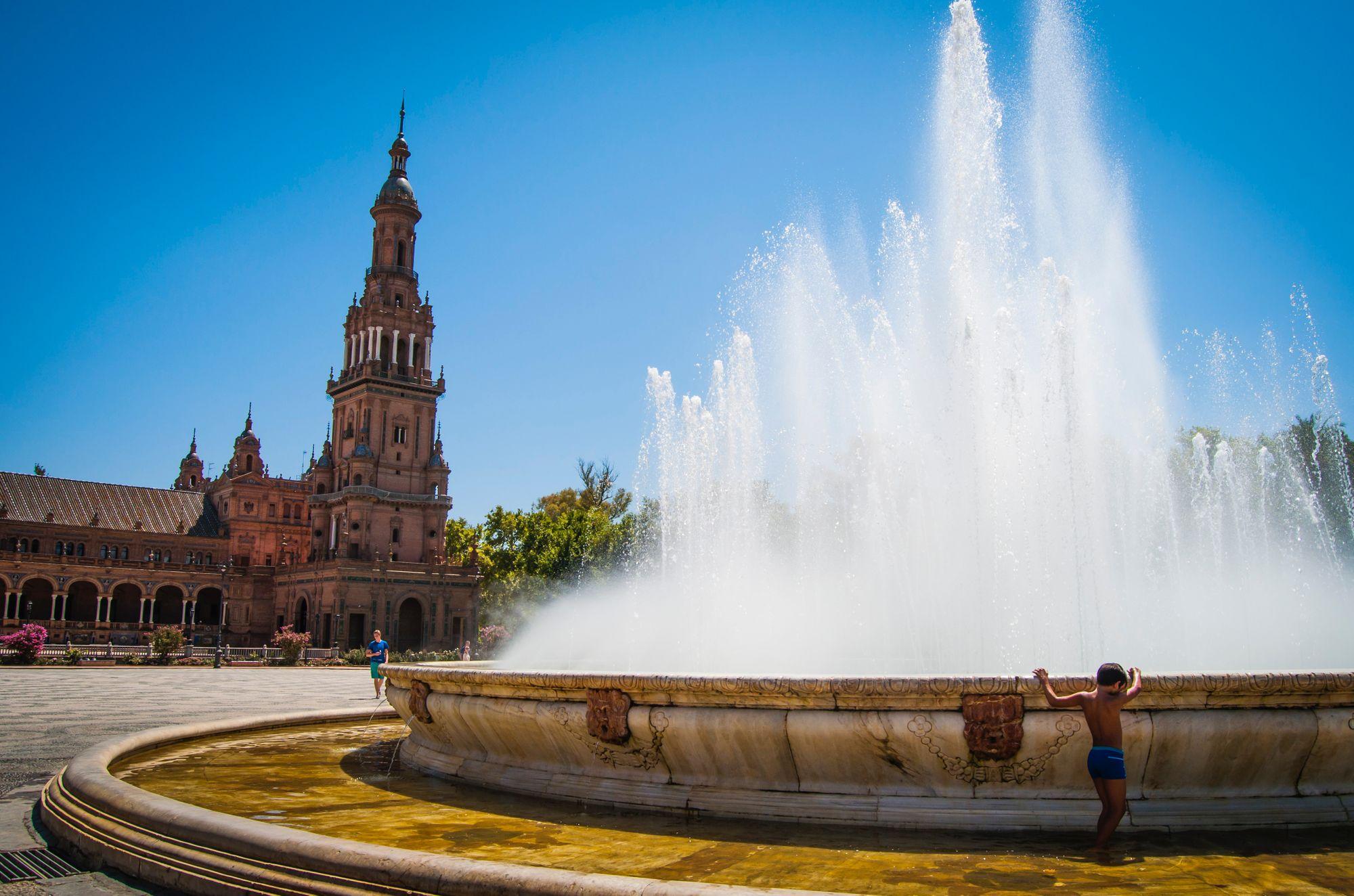 enfant en maillot de bain devant la fontaine de la place d'Espagne à Séville en Espagne
